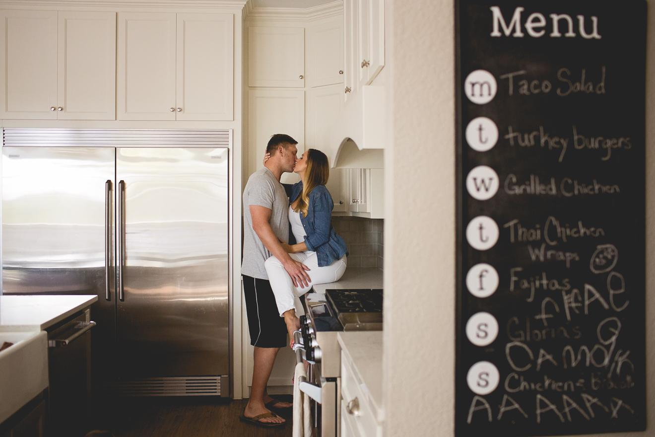 Parents kissing in their kitchen by Southlake family photographer Sunny Mays near Westlake Texas